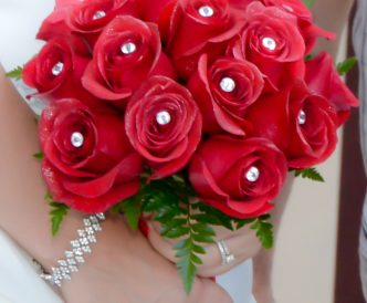 18 rose hand tied bridal bouquet with bright red roses.