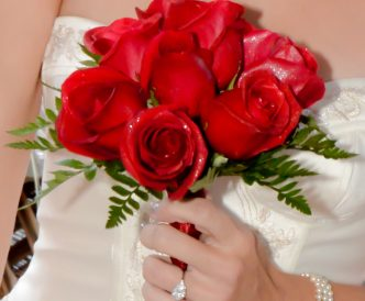 9 rose hand tied bridal bouquet with bright red roses.