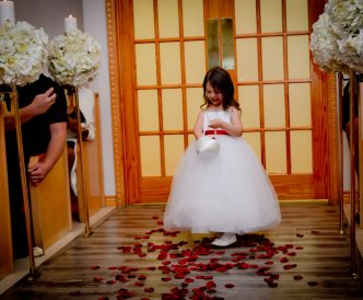 Candid wedding photography: flower girl dropping rose petals.