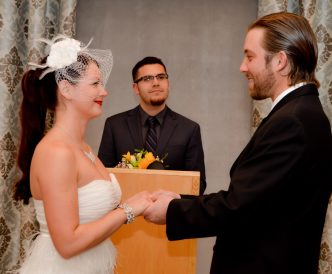 Candid wedding photography: bride and groom exchange wedding vows in chapel