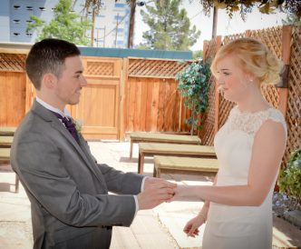Candid wedding photography: bride and groom exchange wedding rings outdoors in the Gazebo.
