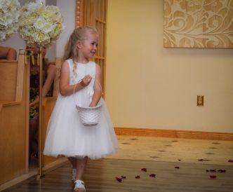 Candid wedding photography: angelic flower girl in chapel.