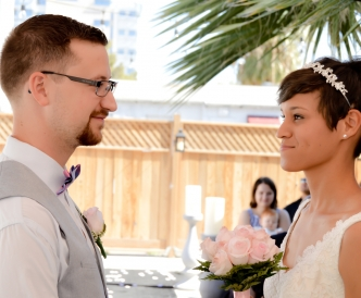 Candid wedding photography: couple exchanging vows of marriage as guests look on.