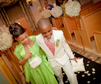 Candid wedding photography: flower girl and ring bearer enter chapel during wedding procession.
