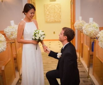 Candid wedding photography: groom meets his bride on one knee in wedding chapel after she enters.