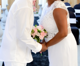 Candid wedding photography: just married couple takes their first kiss as husband and wife.
