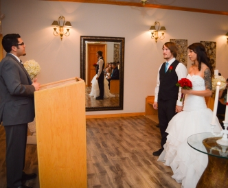 Candid wedding photography: bride and groom listen to opening words of their wedding minister in chapel.