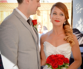 Candid wedding photography: bride and groom welcomed by their wedding minister outdoors in the Pavilion.