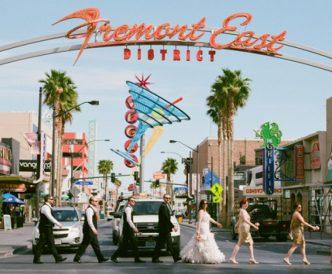 Neon Boneyard Wedding Photography: wedding party crosses street beneath Fremont East sign.