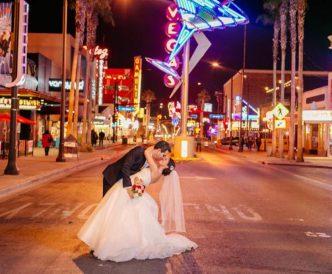 Neon Boneyard Wedding Photography: couple dip kiss beneath neon martini.
