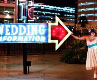 Neon Boneyard Wedding Photography: bride by Wedding Information sign.