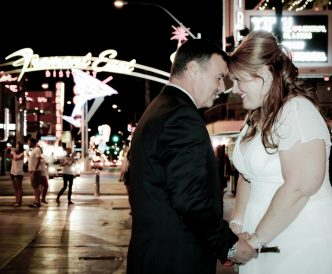 Neon Boneyard Wedding Photography: bride and groom kiss on Fremont Street.