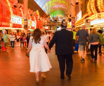 Fremont Street Wedding Photography: bride and groom walk under the bright lights.