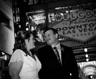 Neon Boneyard Wedding Photography: bride and groom smile by Welcome sign.