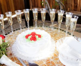 White wedding cake with red rose finish, plates and nicely set champagne flutes ready for guests at reception.