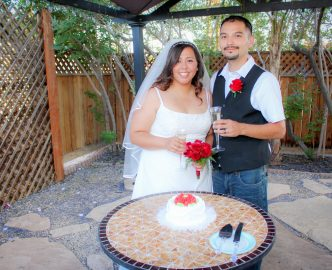 Newly married couple smiles as they prepare to cut the cake during their outdoor reception with guests.