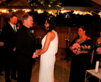 Minister, bride, groom, best man and maid of honor stand in outdoor Gazebo wedding.