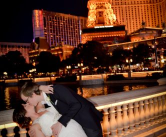 Wedding photography on the Vegas Strip: newly married kiss on Vegas Strip at night.