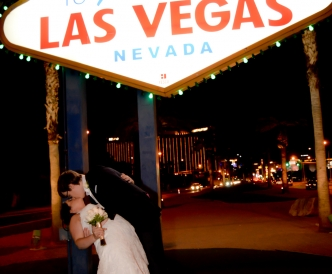 Wedding photography on the Vegas Strip: newlyweds kiss beneath the Las Vegas Welcome sign.
