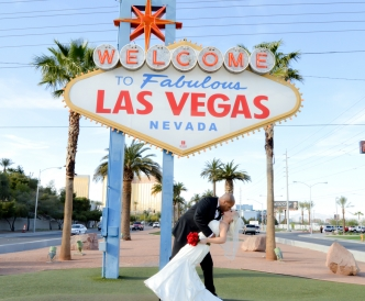 "Wedding photography on the Vegas Strip: bride and groom dip kiss beneath ""Welcome to Fabulous Las Vegas"" sign."