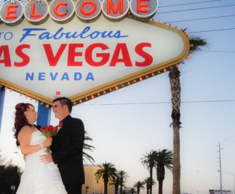 Wedding photography on the Vegas Strip: couple beneath Vegas welcome sign at dusk.