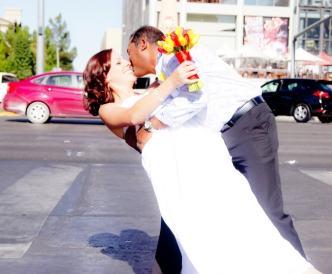 Wedding photography on the Vegas Strip: newly married couple kiss in the middle of Las Vegas Boulevard.