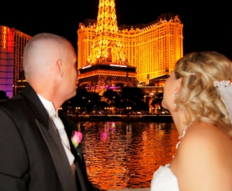 Wedding photography on the Vegas Strip: husband and wife look on as Eiffel Tower in Las Vegas is lit up at night.