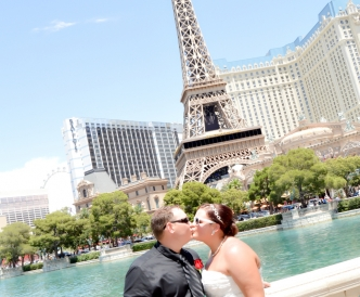 Wedding photography on the Vegas Strip: Kiss beneath the Eiffel Tower replica at Paris Hotel Casino.