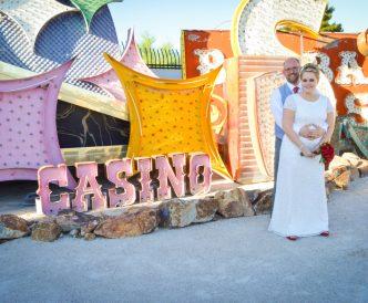 Neon Boneyard Wedding Photography: bride in wedding dress by neon signs.