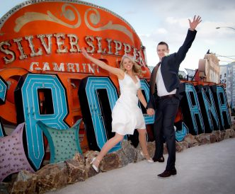Neon Boneyard Wedding Photography: bride and groom leap by Tropicana sign.