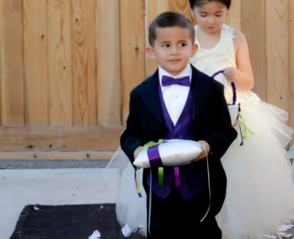 Ring bearer and flower girl proceed the aisle during daytime outdoor wedding ceremony in Le Pavilion.