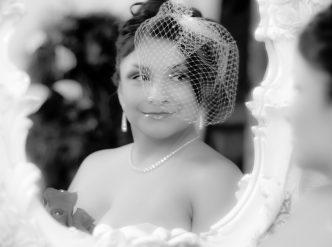 Posed wedding photography: bride smiles in mirror.