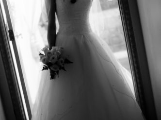 Posed wedding photography: bride in wedding dress black and white against lit background.