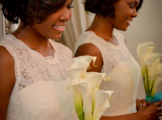 Posed wedding photography: bridal smile with bouquet.