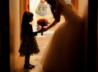 Posed wedding photography: little flower girl brings bouquet to bride.