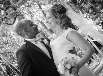 Posed wedding photography: newlyweds celebrate their love in the chapel garden.