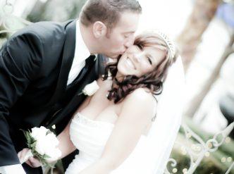 Posed wedding photography: groom kisses his bride's cheek in the chapel garden.