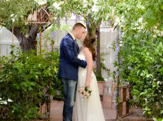 Posed wedding photography: gorgeous daytime trellis kiss for bride and groom.