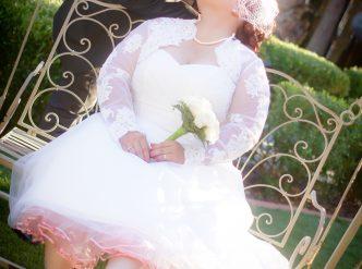 Posed wedding photography: bride on garden swing.