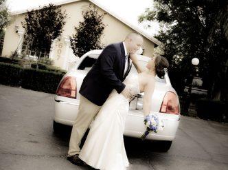 Posed wedding photography: bride and groom at wedding limo.