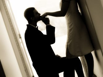 Posed wedding photography: down on one knee, groom kisses bride on the hand.
