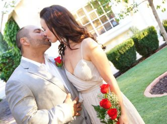 Posed wedding photography: newlyweds kiss in front of the wedding chapel.