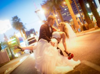 Posed wedding photography: newlyweds dip for a kiss on Las Vegas Boulevard at night.