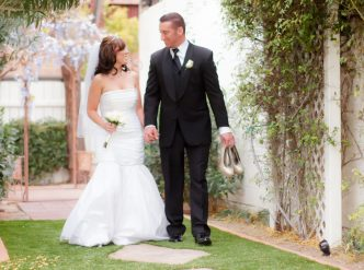 Posed wedding photography: newlyweds stroll in the garden.