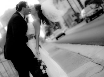 Posed wedding photography: kiss on Las Vegas Boulevard in black and white.