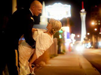 Posed wedding photography: kiss on Las Vegas Boulevard at night.