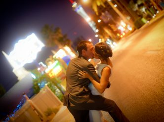 Posed wedding photography: kiss on Las Vegas Boulevard under neon signs of the Strip.