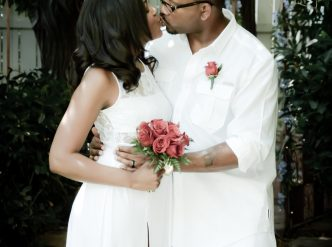 Posed wedding photography: just married couple kisses in the chapel garden.