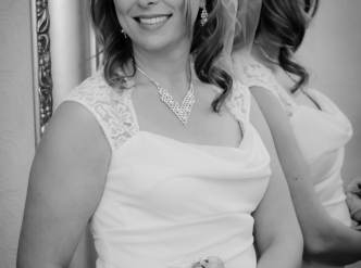 Posed wedding photography: bride with bouquet stands near mirror and smiles.