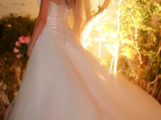 Posed wedding photography: bridal back against amber lighting.